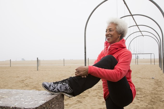 African American woman stretching on beach